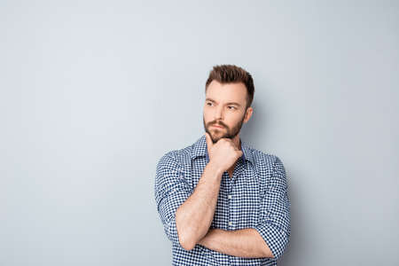 to ponder: Handsome ponder young businessman isolated on gray background