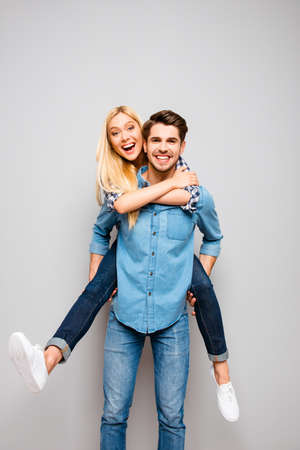 Cute couple in love traveling. Happy man carrying his joyful girlfriend on the back Stock Photo