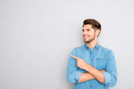 Cheerful young man pointing away on gray background Stock Photo