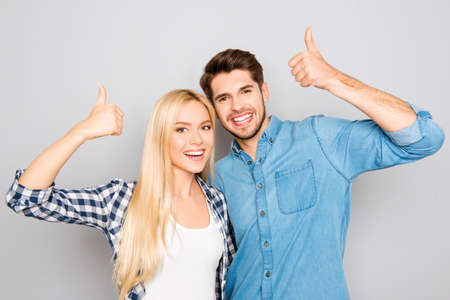 Attractive cheerful young lovers showing thumbs up