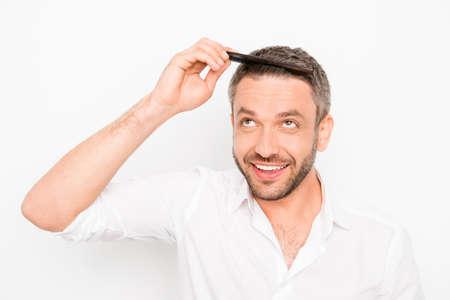 Gut aussehender junger Mann, der seine Haare mit Kamm zu kämmen Standard-Bild - 59056667