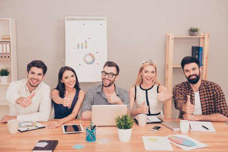 comité d entreprise: photo de l'heureux jeune équipe assis à la table de conférence en souriant et pouce vers le haut