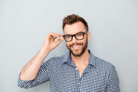 Cheerful smiling young businessman touching his glasses Фото со стока