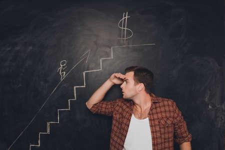 purposeful: Young purposeful man looking at drawn career stairs Stock Photo