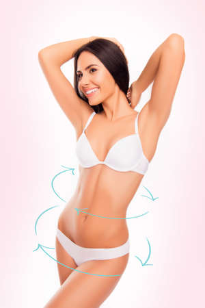 bra beauty: Beautiful happy woman smiling and  showing her healthy slim body with arrows