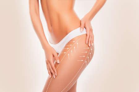 modelos desnudas: Mujer hermosa en forma delgada tocar su cuerpo con flechas aislados en el fondo beige