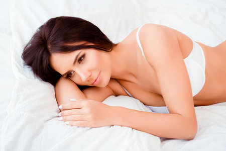 minded: Minded sensual relaxed young woman lying in bed Stock Photo