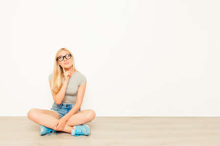 minded: Minded pretty woman sitting on floor and thinking about future idea Stock Photo