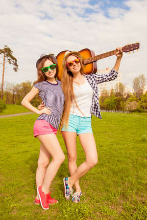 instrumentalist: Pretty sexy girls in hats and glasses walking in park with guitar