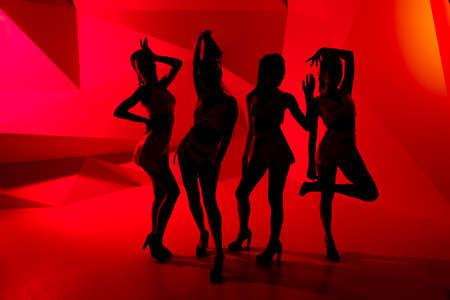 siluetas mujeres: Foto de siluetas de cuatro niñas de postura atractivas en luz roja