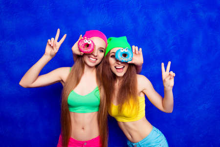 lesbo: Cheerful happy hipster sisters having fun and holding donutes