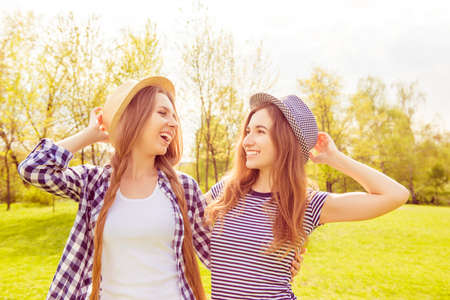 lesbo: Two happy laughing sisters having walk in the park