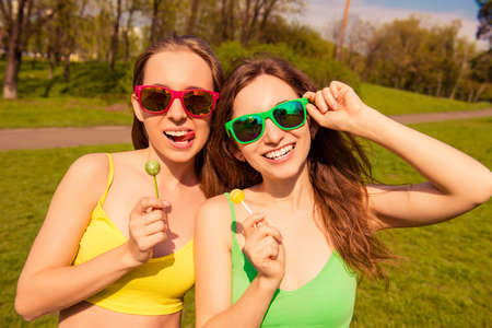 lesbo: Attractive cheerful smiling girls having walk in park with lollipops