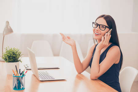 Smart pretty businesswoman in glasses talking on phone with clients