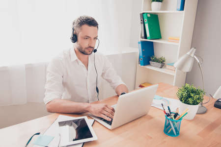 caller: Portrait of bearded young worker of call center Stock Photo