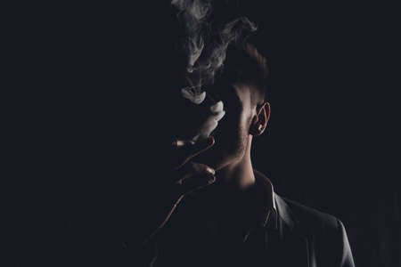 mystery man: Mystery man with cigar and smoke isolated on black background