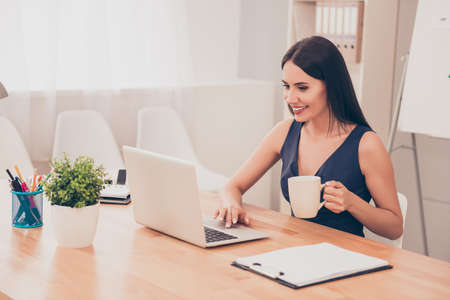 everyday jobs: Happy smiling woman working with laptop and drinking coffee Stock Photo