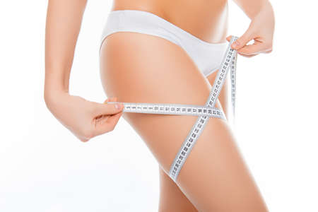 Close up photo of woman measuring her legs size with tape measure Stock Photo