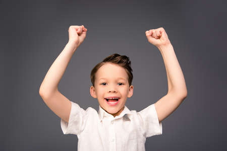 triumphing: Portrait of happy little boy triumphing with raised hands Stock Photo