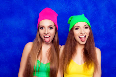lesbo: Comic portrait of happy young women in hats showing tongues