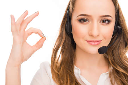 caller: Pretty young  agent of call centre gesturing OK Stock Photo