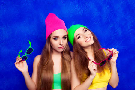 lesbo: Two happy young girlfriends in color hats holding glasses