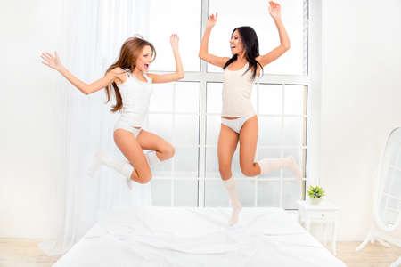 pijamada: Dos chicas alegres bailando en pijamas en cama y la risa Foto de archivo