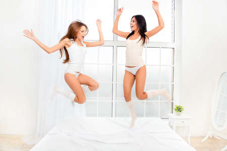 caper: Two cheerful girls in pajamas dancing on  bed and laughing