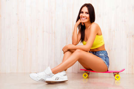 siting: Cheerful smiling young woman siting on skate board