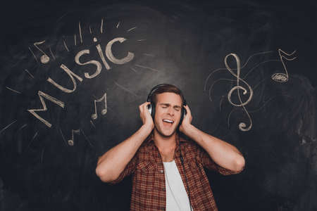 Portrait of handsome music fan in head-phones listening music