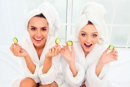 bathrobes: Cheerful smiling woman in bathrobes and towelson their heads holding slices of cucumber