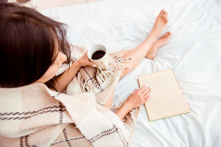 Top view of young woman reading book and basking with plaid and coffee Stock Photo