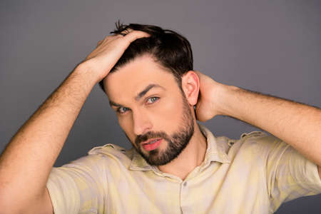 combing hair: Portrait of handsome bearded man combing hair with fingers Stock Photo
