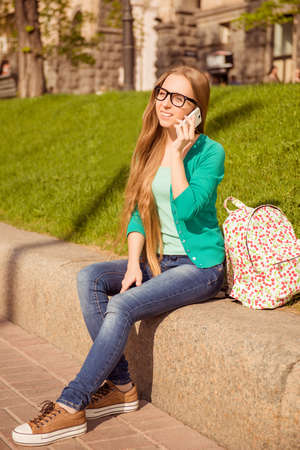 siting: Happy young woman siting on the street and talking on phone