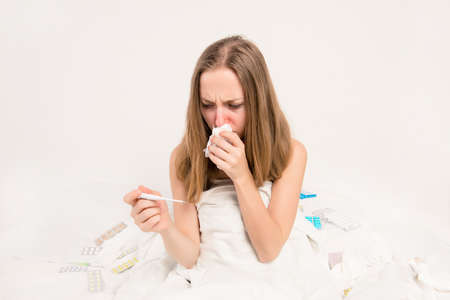 running nose: Portrait of ill woman with fever and running nose holding thermometer Stock Photo