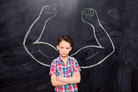 Little boy on backgroung of blackboard with drawn muscles Stock Photo