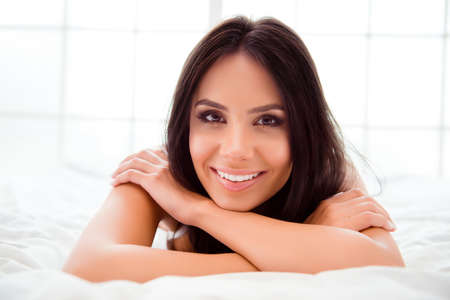 beaming: Pretty woman with beaming smile relaxing and lying in bed Stock Photo