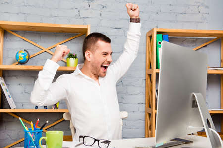 triumphing: Cheerful happy young  man triumphing with raised hands Stock Photo