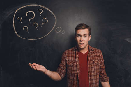 perplexity: Attractive young freelancer at a loss on the background of chalkboard