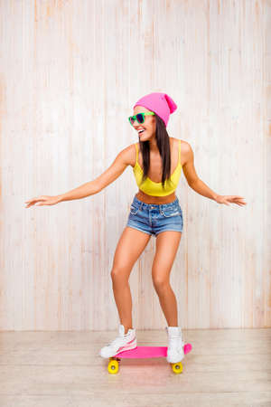 Happy young woman in pnk hat and glasses riding on skateboard