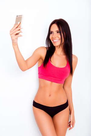 Attractive fit slim woman in black panties making selfie