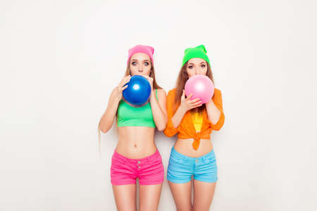 Two hipster girls preparing for party and blowing balloons