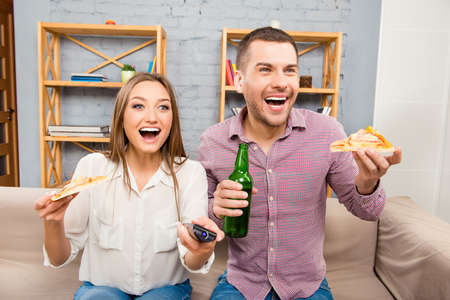atractive: Atractive happy young man and woman watching tv with beer and pizza