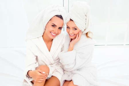 Retrato de dos niñas felices sonriendo en albornoz y turbante Foto de archivo - 60465354