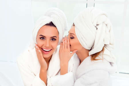 Girl in bathrobe and  towel on her head telling secret to her sister Stockfoto