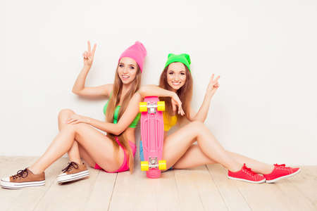 siting: Portrait of  cheerful women siting with skateboard and gesturing with two fingers