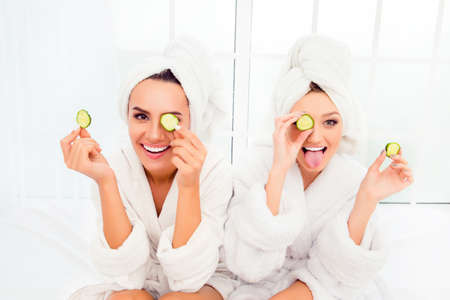 Comic young sisters after shower making mask with cucumber