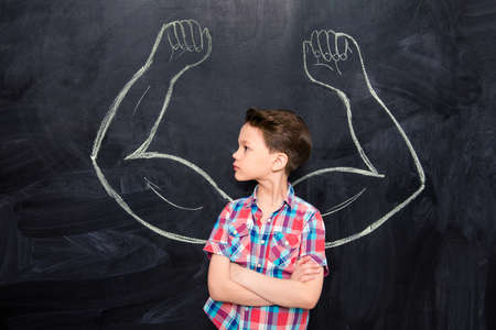 adulthood: Little boy looking at muscles drawn on blackboard