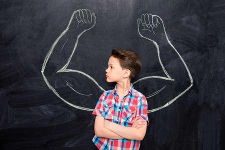 Little boy looking at muscles drawn on blackboard