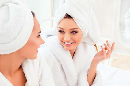 Portrait of happy cheerful girl in robe talking with her friend